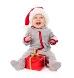 Schätzchen im Sankt-Hut, der mit Weihnachtsgeschenkkasten spielt Lizenzfreie Stockbilder