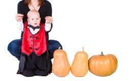Schätzchen im schwarzen Halloween-Mantel mit Kürbis stockbild