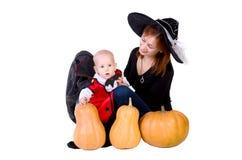 Schätzchen im schwarzen Halloween-Mantel mit Kürbis Lizenzfreies Stockfoto