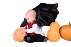 Schätzchen im schwarzen Halloween-Mantel mit Kürbis Lizenzfreies Stockbild