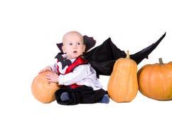 Schätzchen im schwarzen Halloween-Mantel mit Kürbis Lizenzfreie Stockbilder