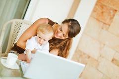 Schätzchen mit der Mutter, die an Laptop arbeitet Lizenzfreie Stockbilder