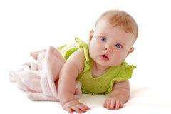 Schätzchen mit hellen blauen Augen streichelt weiche Decke. Lizenzfreies Stockfoto