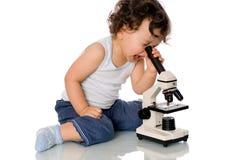 Schätzchen mit Mikroskop. Lizenzfreies Stockfoto