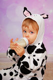 Schätzchen in Trinkmilch des Kuhkostüms von der Flasche Lizenzfreies Stockfoto