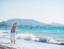 Schätzchen, welches die Mutter steht am Seeufer umarmt lizenzfreie stockfotos