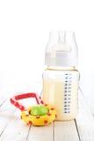 Schätzchenflasche mit Spielzeug Stockbild