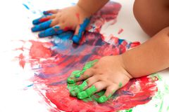 Schätzchenhände, die buntes Mosaik malen. Stockfotografie
