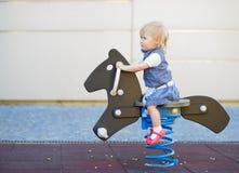 Schätzchenschwingen auf Pferd auf Spielplatz Stockfoto