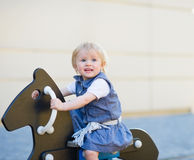 Schätzchenschwingen auf Pferd auf Spielplatz. Seitenansicht Lizenzfreies Stockfoto