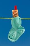 Schätzchensocken auf Wäscheleine mit Eurobanknoten Stockfotografie