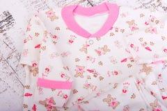 Schätzchenwaren, die an der Wäscheleine hängen Babybluse und Hosenschieber pijama Lizenzfreies Stockfoto