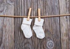 Schätzchenwaren, die an der Wäscheleine hängen Weiße Socken des Babys auf einer Wäscheklammer Stockbild