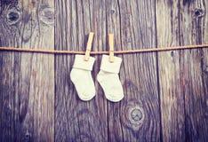 Schätzchenwaren, die an der Wäscheleine hängen Weiße Socken des Babys auf einer Wäscheklammer Lizenzfreie Stockfotos