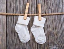 Schätzchenwaren, die an der Wäscheleine hängen Weiße Socken des Babys auf einer Wäscheklammer Lizenzfreie Stockbilder