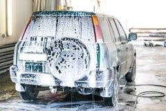 Schäumende Wäsche der Waschanlage Das Auto ist rückwärts Stockfotografie