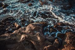 Schäumende Wellen am felsigen Strand Stockfotos