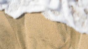 Schäumender Meereswoge, der sich quikly über dem Strandsand wäscht Stockbilder