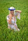 Schön, attraktiv, Blondine mit Kornblumenblaukrone auf dem Gebiet von Getreide lizenzfreie stockbilder