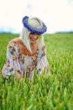 Schön, attraktiv, Blondine mit Kornblumenblaukrone auf dem Gebiet von Getreide lizenzfreies stockfoto
