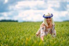 Schön, attraktiv, Blondine mit Kornblumenblaukrone auf dem Gebiet von Getreide lizenzfreie stockfotos