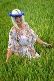 Schön, attraktiv, Blondine mit Kornblumenblaukrone auf dem Gebiet von Getreide stockfotos