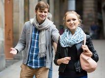 Schön aussehender männlicher Student, der erfreutes Mädchen auf Datum im Freien jagt Stockfotografie