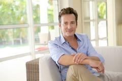 Schön aussehender Mann, der zu Hause sitzt Stockfotos