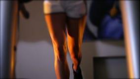 Schön bräunte die weiblichen Beine, die auf einer Tretmühle in der Turnhalle laufen gelassen wurden stock footage