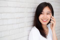 Schön des jungen asiatischen vom intelligenten Telefon und vom Lächeln Frauengespräches des Porträts, die auf Zementziegelsteinhi stockfotografie