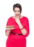 Schön plus die Größenfrau, die mit Kuchen temptating ist Lizenzfreie Stockfotografie