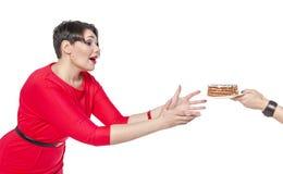 Schön plus die Größenfrau, die mit Kuchen temptating ist Lizenzfreies Stockfoto
