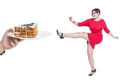 Schön plus die Größenfrau, die weg das ungesunde Lebensmittel lokalisiert kämpft Lizenzfreies Stockbild