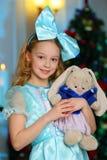 Schön, recht blondes Kindermädchen auf dem Hintergrund eines Baums des neuen Jahres bezaubernd Lizenzfreies Stockbild