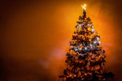 Schön romantischer verzierter Weihnachtsbaum mit multi farbigen Lichtern auf warmem Hintergrund und Raum für Ihren Text Stockbild