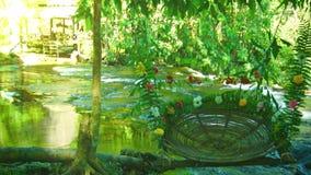 Schön verzierter Stuhl im Schatten von Bäumen nahe dem Wasserfall Lizenzfreies Stockfoto