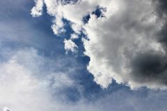 Schön von der Dunkelheit und von den hellen weißen Farben der Wolke im blauen Himmel Lizenzfreie Stockfotografie