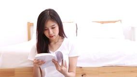 Schön von der jungen asiatischen Frau des Porträts entspannen Sie sich sitzendes Lesebuch auf Schlafzimmer zu Hause stock video footage