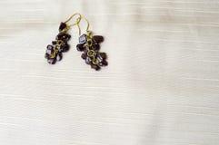 Schön, weiblich, Modeohrringe von den braunen dunklen Steinen, bernsteinfarbig auf einem Hintergrund des beige Gewebes lizenzfreies stockbild