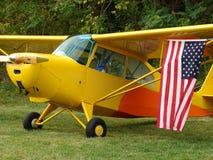 Schön wieder hergestellter klassischer Champion Aeronca 7AC, der US-Flagge anzeigt Stockfotografie