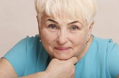 Schöne ältere blonde Frau im blauen Kleid Stockbild