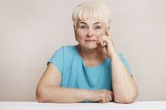 Schöne ältere blonde Frau im blauen Kleid Lizenzfreie Stockfotos