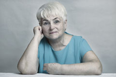 Schöne ältere blonde Frau im blauen Kleid Stockfoto