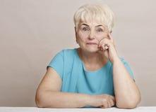 Schöne ältere blonde Frau im blauen Kleid Lizenzfreies Stockfoto