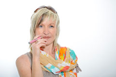 Schöne ältere Frau des blonden Haares, die elektronische Zigarette raucht Stockfoto