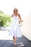 Schöne ältere Frau, die auf Bürgersteig am Telefon geht Stockfotos