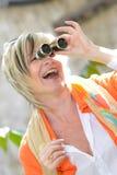 Schöne ältere Frau, die durch Ferngläser schaut Stockfoto