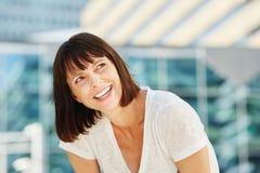 Schöne ältere Frau, die weg lachend schaut Stockbild