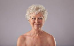 Schöne ältere Frau hemdlos gegen grauen Hintergrund Lizenzfreies Stockfoto