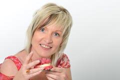 Schöne ältere Frau im rosa Kleid gelbes und rosa maca essend Lizenzfreie Stockbilder